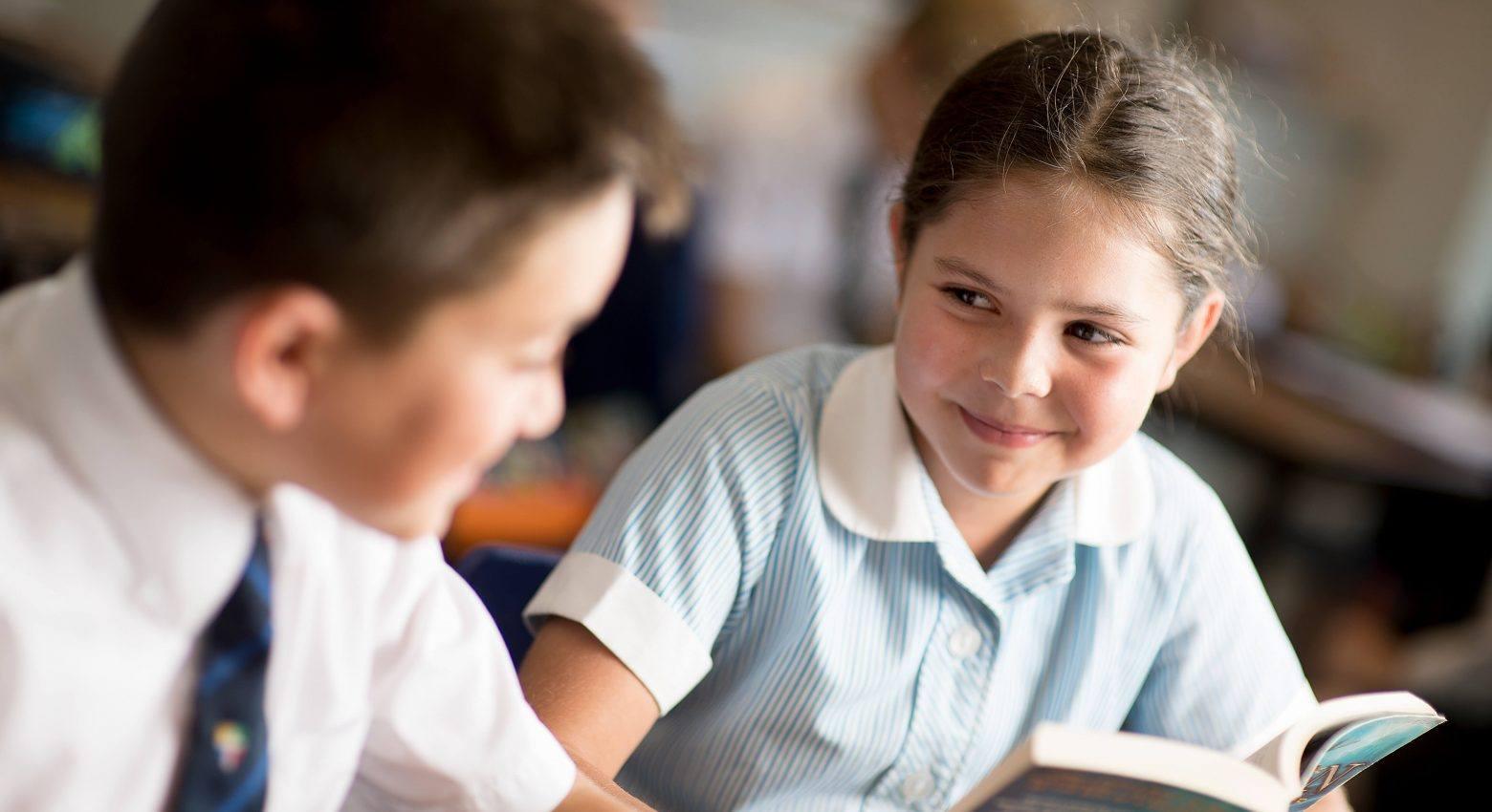 School girl reading to school boy