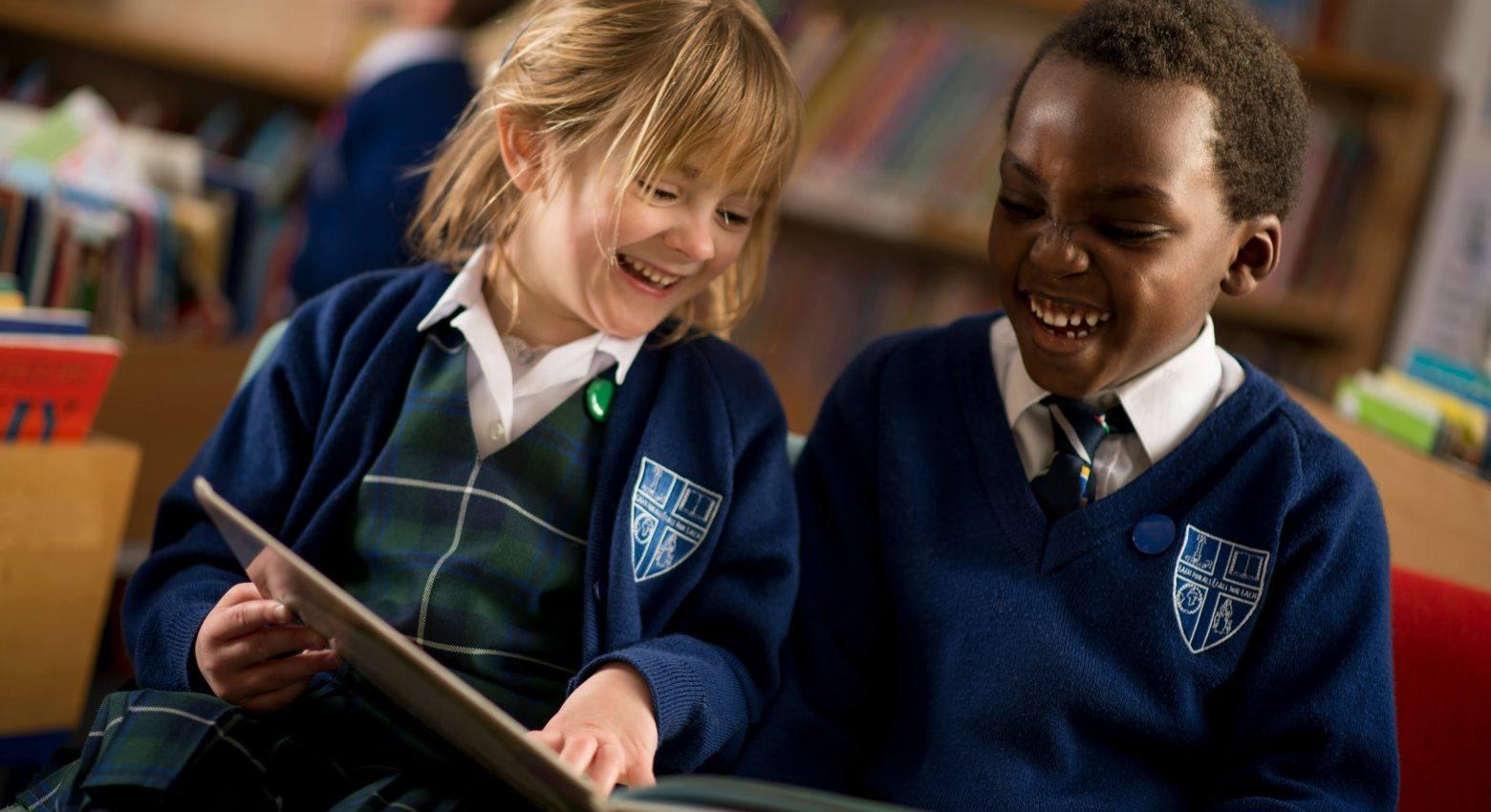 school children enjoying a book