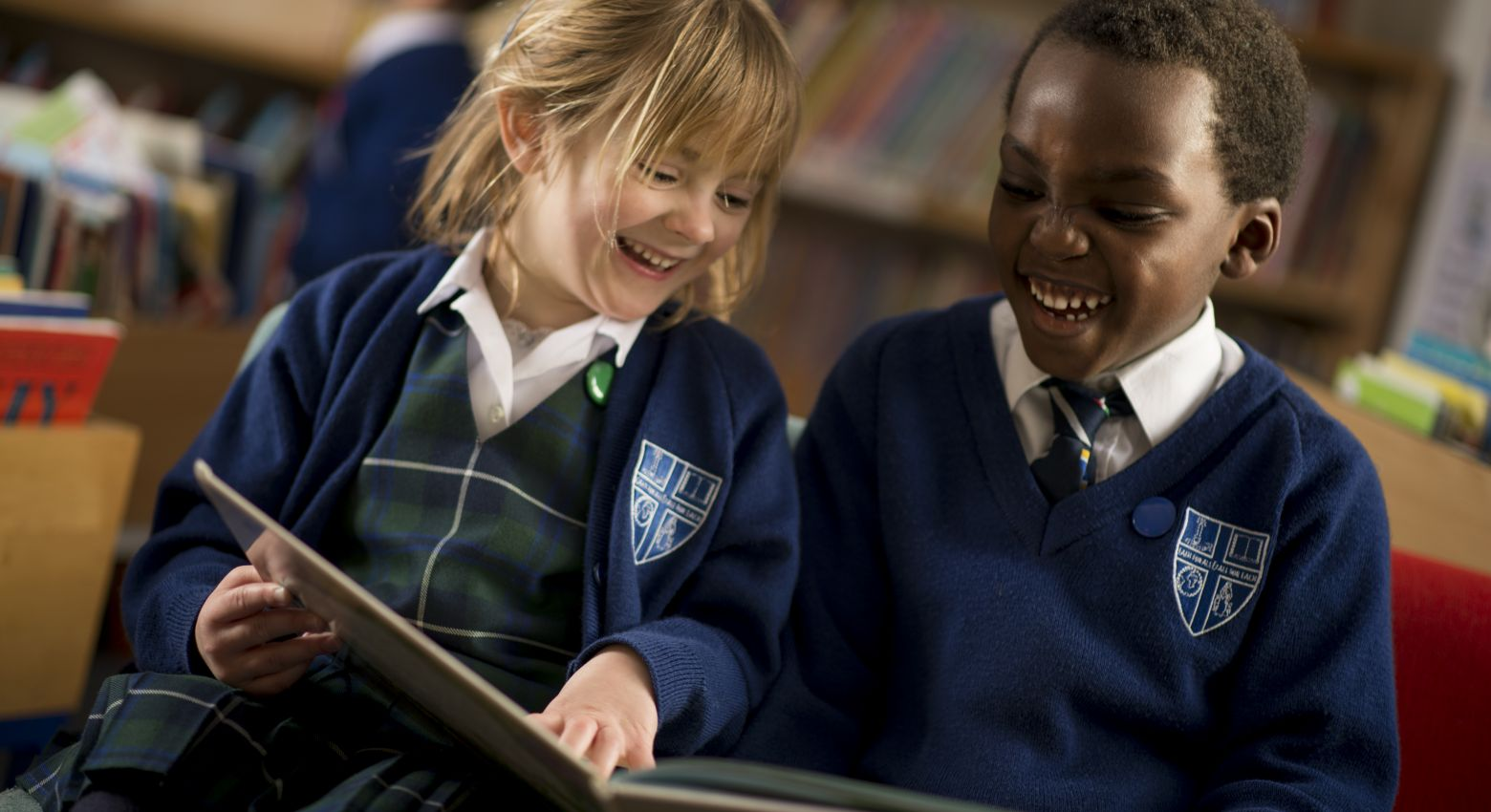 boy and girl laughing at a book