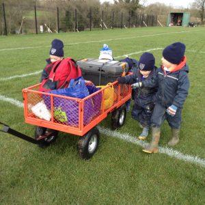 children walking next to a cart of outdoor equipment
