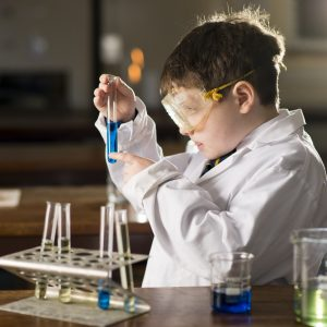 child in lab coat holding up test tubes next to a bunsen burner